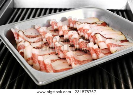 Neat Rows Of Pre-cooked Bacon Slices On A Tray
