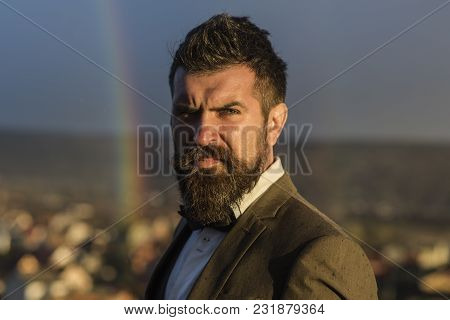 Guy with concentrated face in suit. Hipster with stylish hairdo in front of sky with rainbow. Barber and hairdo concept. Man with beard and mustache and scenery with rainbow on background, defocused. poster