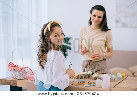 Mother And Cute Little Daughter Painting Easter Eggs At Home