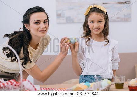 Young Mother And Daughter Doing Egg Tapping On Easter