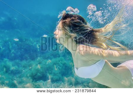 Girl And Small Fish Swimming Underwater Portrait. Sea Summer Blue Water Background With Bubbles