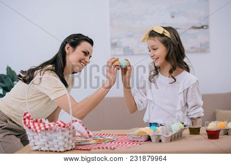 Happy Young Mother And Daughter Doing Egg Tapping On Easter