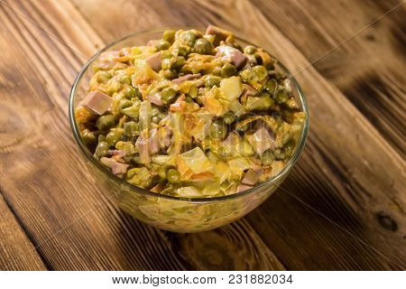 Mayonnaise Salad With Sausage, Green Pea, Carrot And Onion On Wooden Table