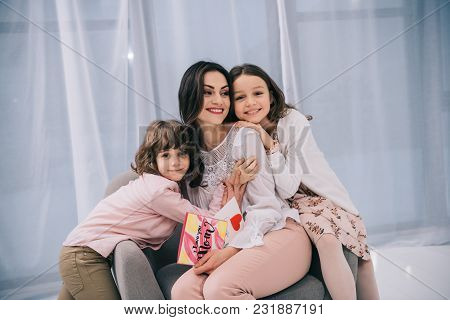 Children Sitting On Comfy Armchair With Mother On Mothers Day