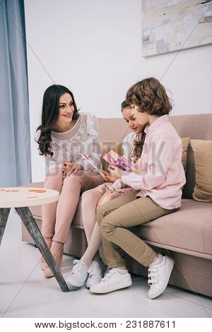 Kids Sitting With Mother On Sofa And Showing Her Greeting Cards For Mothers Day