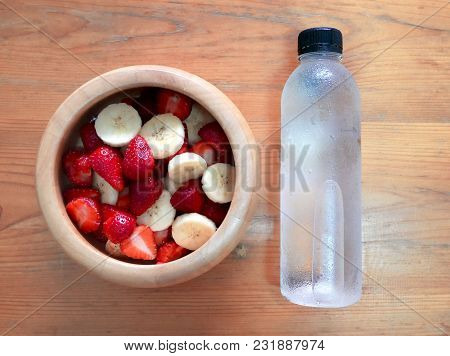 Strawberry And Banana In Wooden Bowl With Mineral Water. Healthy Diet Eating And Weigh Loss Concept.