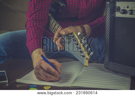 Hipster Musician Sits On The Couch With An Electric Guitar And Records The Notes Of His Melody