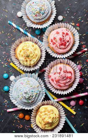 Sweet cupcakes with colorful decor and candies. Top view
