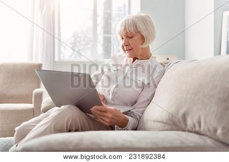 Extra Income. Charming Elderly Woman Sitting On The Couch And Working On Her Laptop, Searching The W