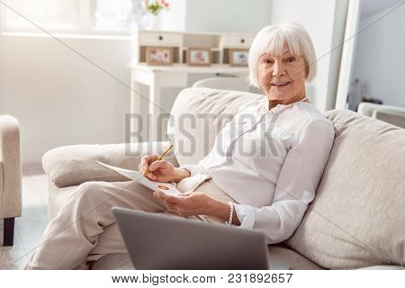 Skilled Professional. Upbeat Senior Woman Sitting On The Sofa And Posing For The Camera While Workin