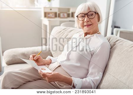 Knowledge Is Power. Beautiful Cheerful Elderly Woman Sitting On The Sofa And Examining The Charts On
