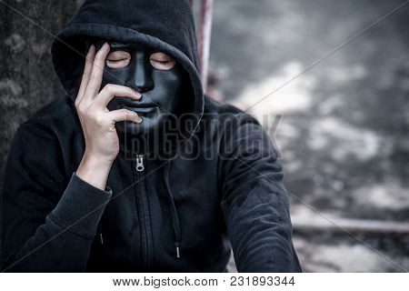 Mystery Man In Black Mask With Hoody Jacket Close His Eye Thinking Of Something. Feeling Stressed Or