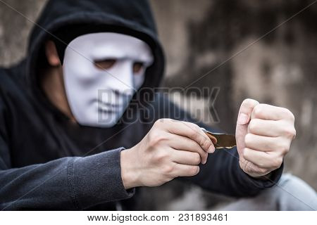 Mystery Man In White Mask Wearing Hoody Jacket Try To Cut His Wrist With The Debris Of Broken Bottle