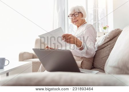 Skilled Analyst. Upbeat Elderly Woman Sitting On The Sofa And Studying The Research Data While Looki