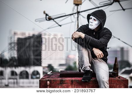 Mystery Man In White Mask With Hoody Jacket, Sitting And Hugs His Knees Up With Broken Empty Bottle.
