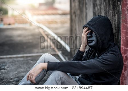 Mystery Man With Black Mask And Hoody Jacket In Headache Gesture Feeling Stressed And Depressed Whil
