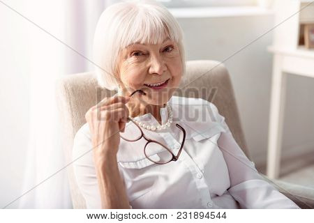 Delicate Beauty. The Close Up Of A Pretty Elderly Woman Posing For The Camera, Having Removed Her Ey