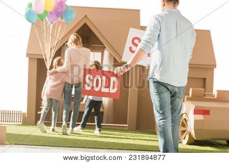 Man Holding Sold Signboard With Young Family Moving Into New Cardbord House Isolated On White