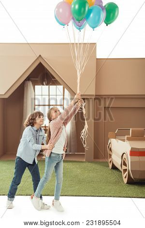 little kids with colorful helium balloons isolated on white poster