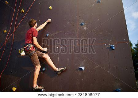 Sporty Man Practicing Rock Climbing In Climbing Gym Artificial Rock Training Wall Outdoors. Young Ta