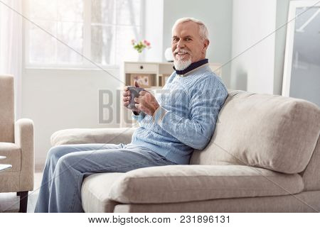 Tasty Drink. Upbeat Senior Man Sitting On The Sofa In The Living Room And Smiling At The Camera Whil