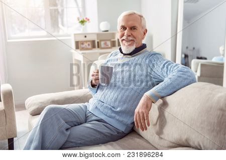 Favorite Delicious Drink. Upbeat Senior Bearded Man Sitting Comfortably On The Couch And Posing For