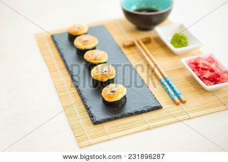 Hot Sushi Roll Sushi Rolls On Black Slate Surface. Japanese Food.