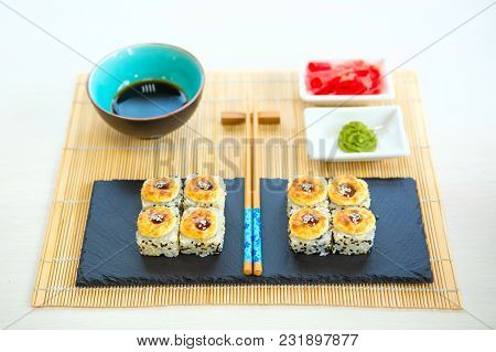 Maki Sushi With Sea Fish And Cream Cheese On Table. Japanese Cuisine. Roll Sushi Set On A Black Slat