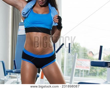 Young, Athletic, Tanned Girl In The Gym With A Towel Around Her Neck. Sportswear. The Girl Wipes Her