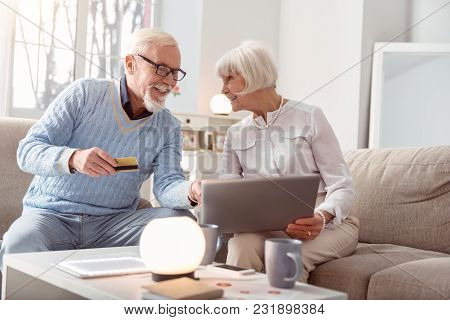 We Are Shopaholics. Upbeat Elderly Couple Shopping Online Together And The Man Pointing At The Lapto