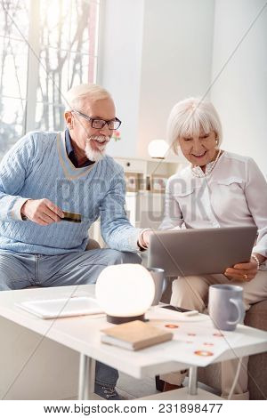 We Love Shopping. Upbeat Elderly Man And His Wife Choosing An Item In The Online Shop, Pointing At I