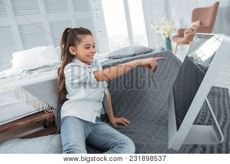 Computer Monitor. Positive Cheerless Cute Girl Smiling And Looking At The Monitor While Pointing At