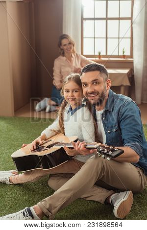 Happy Father And Daughter Playing Guitar On Grass In Front Of Cardboard House With Mother Sitting In
