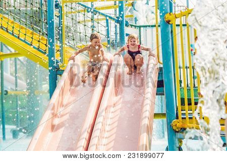 Boy And Girl Have Fun In The Water Park.