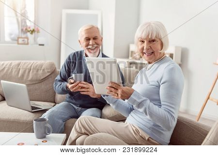 Nice Morning. Cheerful Elderly Couple Sitting In The Living Room, Reading Posts In The Social Media