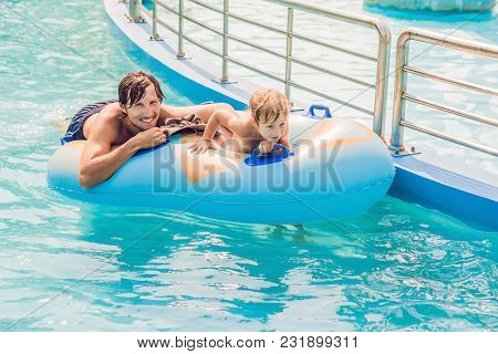 Father And Son Have Fun At The Water Park.