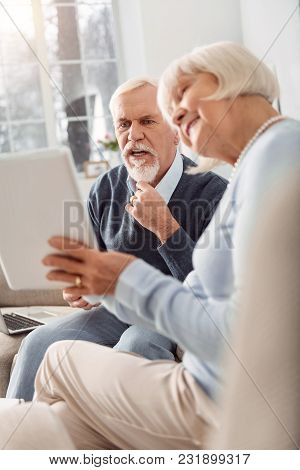 Shocking Content. Charming Elderly Lady Showing Her Husband A Video On The Tablet While He Looking S