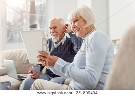 Quality Time Together. Upbeat Elderly Husband And Wife Sitting In The Living Room And Watching A Vid