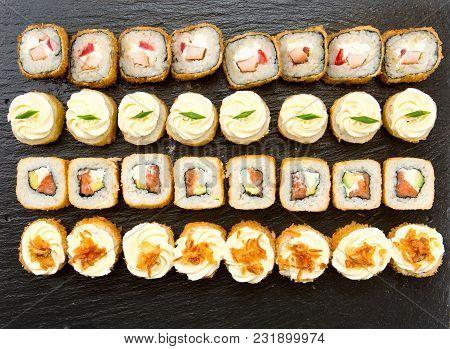 Freid Sushi Rolls Set Served On Black Stone Slate On White Background.