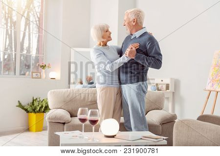 Together Forever. Happy Elderly Couple Dancing Waltz Together In The Living Room And Looking At Each