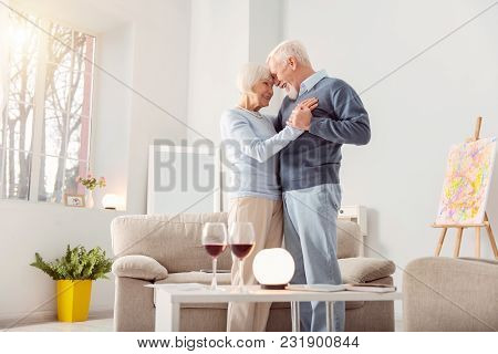 Deep In Love. Pleasant Elderly Couple Dancing Waltz In The Living Room And Leaning Their Foreheads A