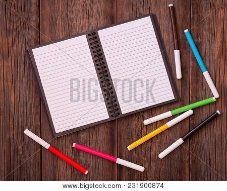 Open Notebook And Colored Felt-tip Pens On A Wooden Background