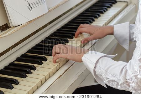 Girl Playing On White Piano. Hands Of A Girl Pressing Piano Keys Close-up.