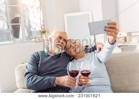 Capturing Happy Moment. Joyful Senior Husband And Wife Cuddling On The Couch And Taking A Selfie Whi