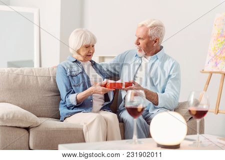 Happy Anniversary. Charming Elderly Man Congratulating His Beloved Wife With Wedding Anniversary And