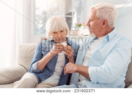 Calm Down. Loving Senior Man Sitting On The Couch Next To His Wife, Hugging And Consoling Her While