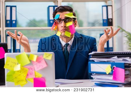 Businessman with reminder notes in multitasking concept