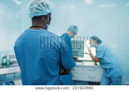 Rear View Of Multicultural Doctors Looking At Patient X-ray