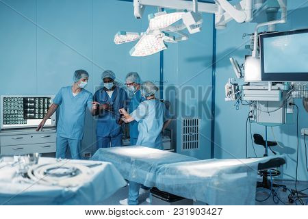 View Of Four Multicultural Surgeons In Operating Room