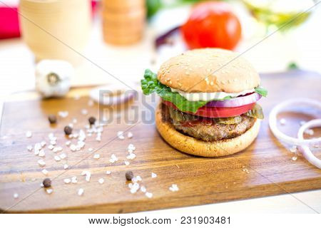 Homemade Burger With Beef, Fried Bacon And Onion On Wooden Cutting Board.